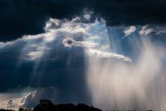 Nubes, sol y lluvia de tormenta en el campo imagen de archivo