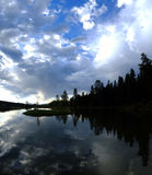 Nubes y agua de los árboles de pino de la silueta del lago Fotografía de archivo libre de regalías