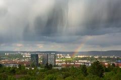 Nubes y arco iris espectaculares sobre ciudad Fotografía de archivo libre de regalías