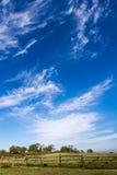Nubes y campo Wispy Imagen de archivo libre de regalías
