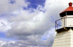 Nubes y faro Imagenes de archivo