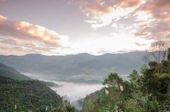 Nubes y niebla hermosas entre paisaje de la montaña imagenes de archivo