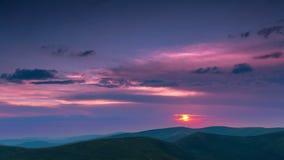 Nubes y puesta del sol sobre las montañas Lapso de tiempo 4K