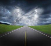 Nubes y relámpago del temporal de lluvia con la carretera y la hierba de asfalto Fotos de archivo libres de regalías