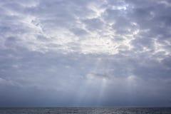Nubi ardenti in cielo con i raggi di sole sopra il lago Ontario Immagine Stock