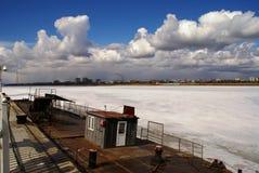 Nubi bianche sopra il fiume congelato Immagine Stock