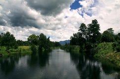 Nubi di tempesta sopra il fiume fotografia stock