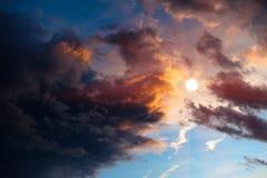Nubi drammatiche di tramonto intorno al sole Immagine Stock