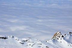Nubi e nebbia qui sopra, paesaggio di inverno nelle alpi Immagini Stock