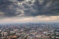 Nubi grige scure di autunno sotto la grande città Immagine Stock