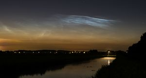 Nubi nottilucenti sopra un canale nei Paesi Bassi immagine stock
