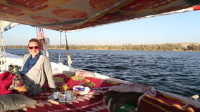Nubian man and female tourist sailing with felucca on the Nile river