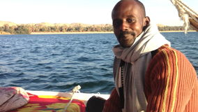 Nubian man looking a camera and talking while sailing felucca on the Nile