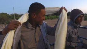 Nubian man smoking cigarette and making turban with scarf stock footage