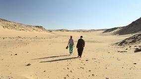 Nubian-Mann, der mit weiblichem Touristen in der Wüste geht stock footage