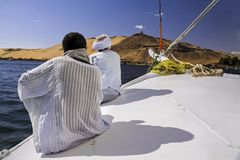 Nubian Men Sailing on Nile River in Aswan Egypt. Nubian Men Wearing Traditional White Desert Clothing Sitting on Felucca Boat Deck and Sailing Down the Nile Royalty Free Stock Photos