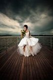 Nubile fiancée!. A pretty young lady on deck in a white wedding dress holding a wedding bouquet Royalty Free Stock Images