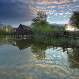 Nubla-se a reflexão na água com watermill Imagem de Stock Royalty Free