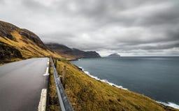 Nublado y Windy Evening View del camino, del océano y de la isla en el horizonte Faroe Island, Dinamarca, Europa Imagen de archivo