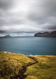 Nublado y Windy Evening View del camino, del océano y de la isla en el horizonte Faroe Island, Dinamarca, Europa Imagen de archivo libre de regalías