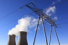 Nuclear energy. Chimneys of a nuclear power plant with a pylon for renewable energy on blue sky background Stock Images