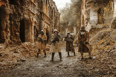 Nuclear post-apocalypse survivors. Nuclear post-apocalypse. Survivors in tatters and gas mask on the ruins of the destroyed city Royalty Free Stock Image
