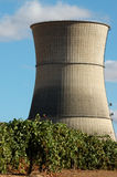Nuclear power cooling tower. A tall concrete cooling tower of at a nuclear power generating station next to an agricultural field Stock Photos