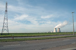 Nuclear power plant. Smoking cooling towers of modern nuclear power plant with road or highway in foreground Stock Photos