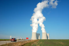 Nuclear power plant. Landscape with a nucler power station and its fuming cooling towers Stock Photos