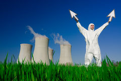 Nuclear power plant. Man wearing protective suit standing in front of a nuclear power plant holding arrows pointing upwards stock photo