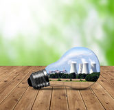 Nuclear power plant in bulb. On wooden table Stock Photo
