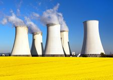Nuclear power plant, cooling tower, field of rapeseed Stock Images