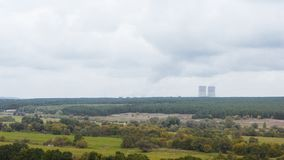 Nuclear power plant in the countryside. Nuclear power plant in the place full of trees and fields. Some rural houses on the foreground of the photo stock image