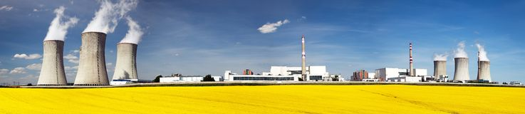 Nuclear power plant Dukovany with golden glowering field. Of rapeseed - Czech Republic - two possibility for production energy Royalty Free Stock Image