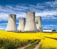 Nuclear power plant and field of rapeseed. Nuclear power plant Dukovany with golden glowering field of rapeseed and rural road - Czech Republic - two possibility Royalty Free Stock Photography