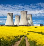 Nuclear power plant, field of rapeseed and rural road Stock Image