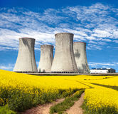 Nuclear power plant, field of rapeseed and rural road. Nuclear power plant Dukovany with golden glowering field of rapeseed and rural road - Czech Republic - two Royalty Free Stock Photography