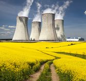 Nuclear power plant, field of rapeseed and rural road. Nuclear power plant Dukovany with golden glowering field of rapeseed and rural road - Czech Republic - two Royalty Free Stock Photos