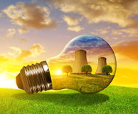Nuclear power plant in light bulb. Nuclear power plant in light bulb at sunset Stock Photo