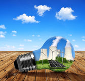 Nuclear power plant with solar panel and wind turbines in lightbulb. Stock Photos