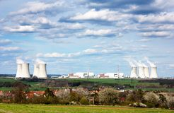 Nuclear power plant and spring time villag. View of nuclear power plant and spring time village - life neat the nuclear plant Royalty Free Stock Photo