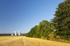 Nuclear Power Plant. A nuclear power station with hill landscape and blue sky, a harvested golden field as foreground Stock Images