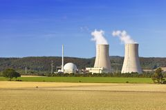 Nuclear Power Plant. A nuclear power station with hill landscape and blue sky. Two motion blurred cyclists in the foreground Stock Photography