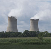 Nuclear Power Plant. Two boiling water reactor units of the Limerick nuclear power plat northwest of Philadelphia.  The emitted water vapor merges with a cloud Royalty Free Stock Image