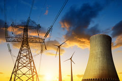 Nuclear power plant with wind turbines and electricity pylon in the sunset. Royalty Free Stock Photo