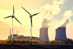 Nuclear power plant and wind turbines. At sunset Royalty Free Stock Image