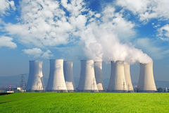 Nuclear power plant with yellow field and big blue clouds Royalty Free Stock Image