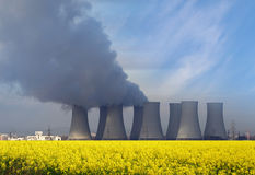 Nuclear power plant with yellow field and  clouds. Stock Photo