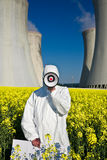 Nuclear Power Protest. A metaphorical image of an environmental activist with a loudspeaker, protesting against a nuclear plant installation royalty free stock photo