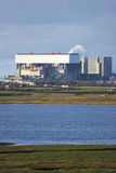 Nuclear Power Station. Photo of a nuclear power station in middle distance with a stretch of water in front. Cloudy sky behind Royalty Free Stock Photo